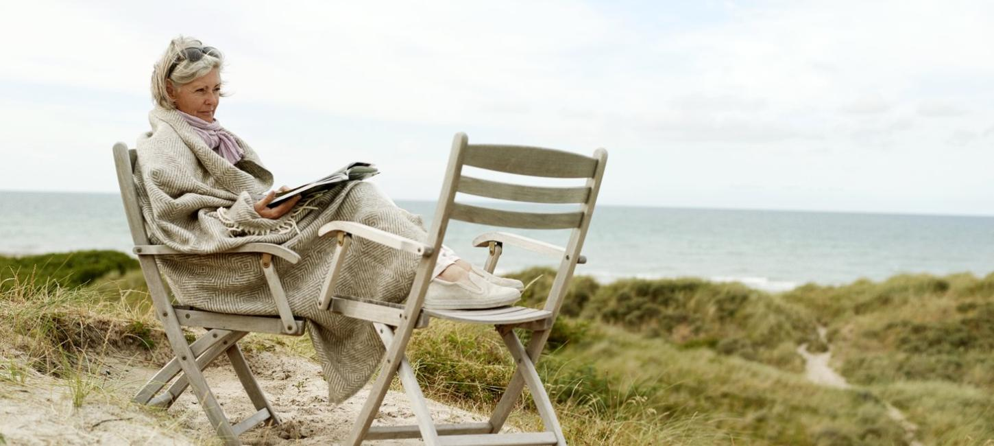 Woman sitting in a chair on the beach, reading a book, in West Jutland