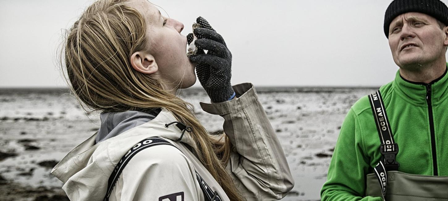 An girl eats a fresh oyster at the Wadden Sea National Park in Denmark