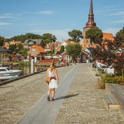 A woman walks beside the harbour in Nysted, Lolland Falster, Denmark