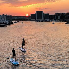 A couple paddleboard at sunset in the Teglholm district of Copenhagen
